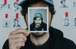 Portrait of Yoni Wolf holding a photo of himself in front of his face.