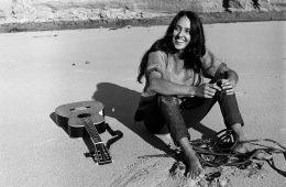 Folk singer Joan Baez strumming her guitar on the beach near her home.