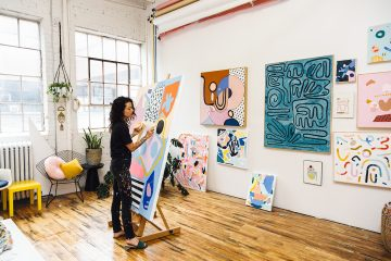 Ashley Mary painting on canvas in her studio.