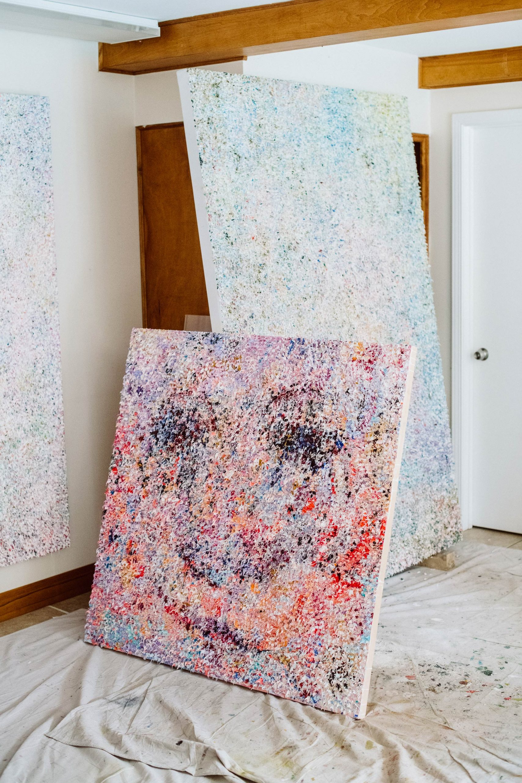 A small painted canvas leaning up against two larger white painted canvases.