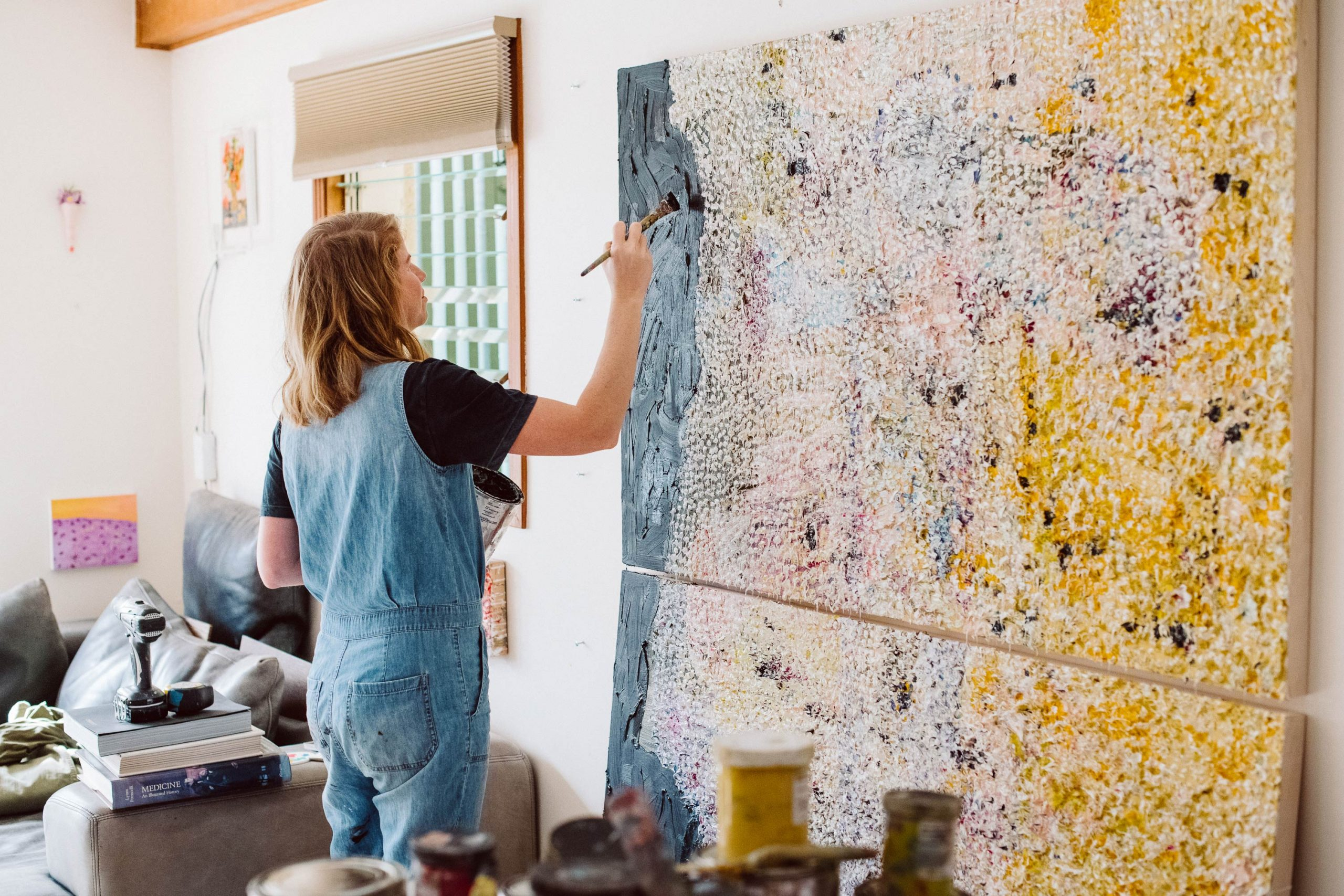 Vanessa Prager painting a large, multicolored canvas.