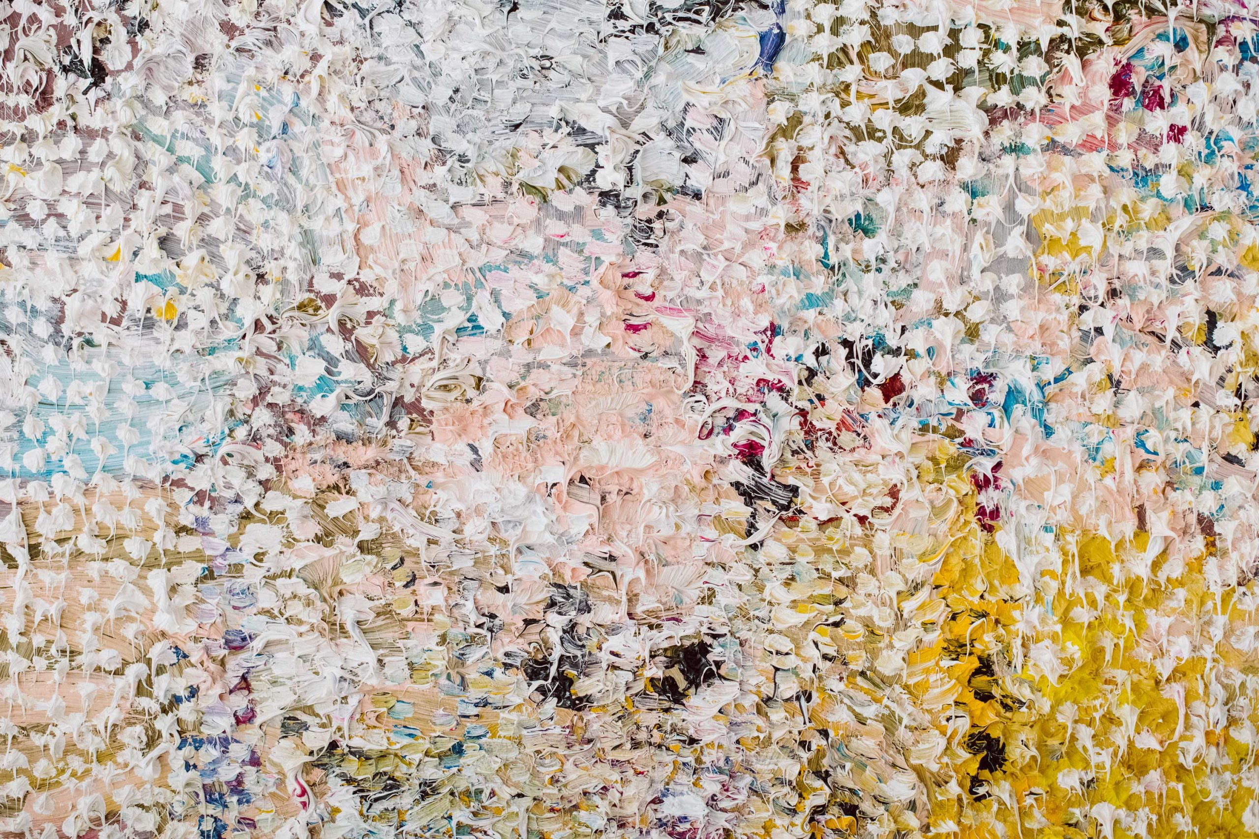 A close up image of a textured and multicolored painting.