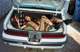 Woman laying in trunk of car in a Rusty Cuts jumpsuit.