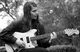 Alex Lahey sitting down and playing her guitar.