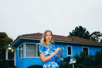Singer Julia Jacklin wearing a blue dress and standing in front of a blue house.