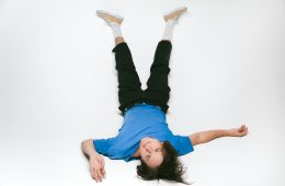 Whitmer Thomas lays on the floor looking upside down at the camera.